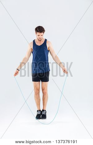 Full length portrait of a man jumping with skipping rope isolated on a gray background