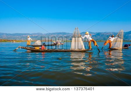 Inle, Myanmar-December 25: The local fishermen are fishing by boat in unique style. By using their feet to control the boat on famous lake on December 25, 2013 in Inle, Myanmar.