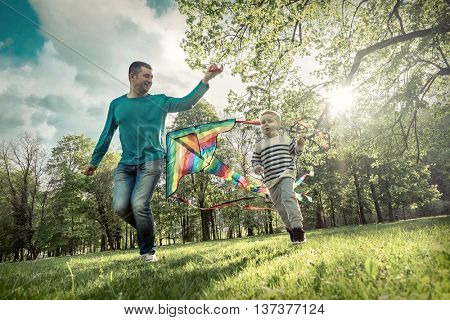 Runnings little boy and father flies with them kite in the park under sunligt.