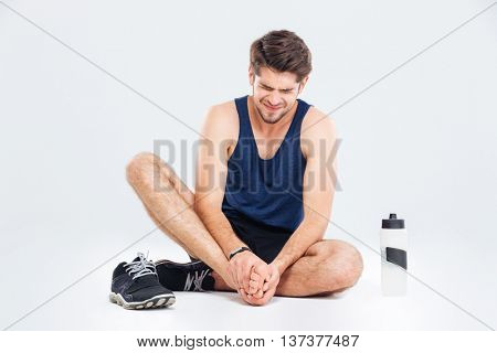 Fitness man sitting and suffering with foot pain over white background