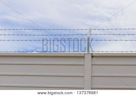 The concrete fence with the barbwire on the top