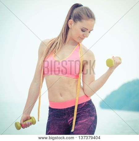 Slim Girl In Sportswear With Centimeter Exercising With Dumbbells On Beach, Sports Lifestyle, Slimmi