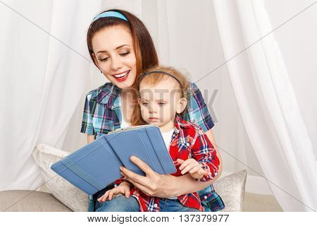 Mother and daughter read the e-book. Young mother and baby daughter hugging sitting on the floor. Girls dressed in plaid shirt. Family education