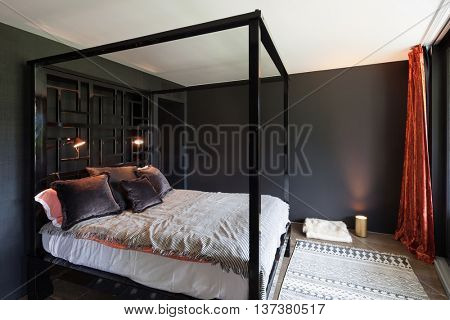 Wooden canopy bed and carpet on the floor, black walls