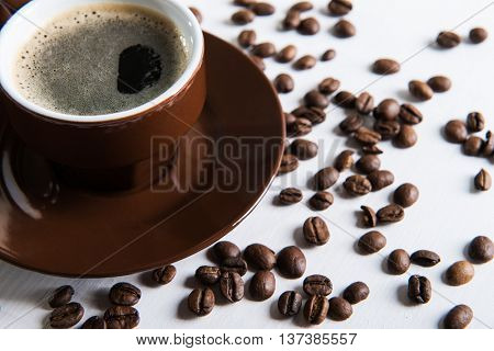 Brown cup with coffee and coffee seed on the table