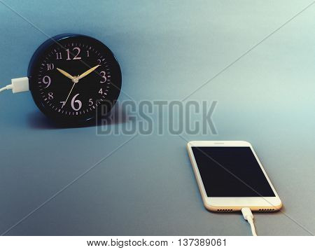 Smart phone charging time from clock with vintage filter. Concept of smart phone take much time smart phone addiction phubbing game or social network issues.