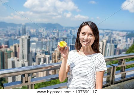 Woman holding famous Hong Kong food of egg tart