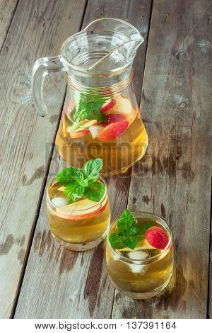 Two glass and carafe of green tea with mint and apples closeup