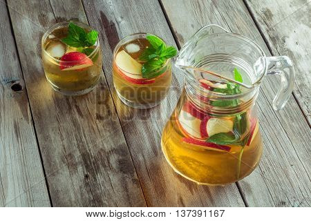 Two glass and carafe of green tea with mint and apples