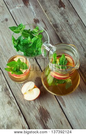 Carafe and a glass of cool green tea with apples and mint