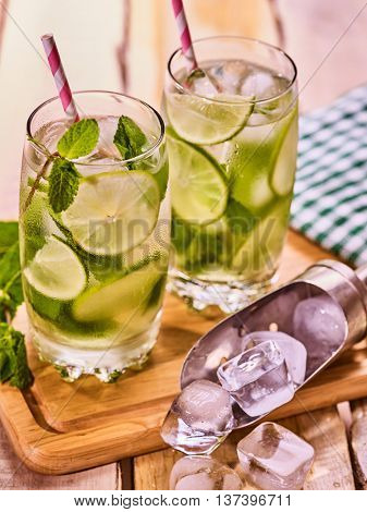 Alcohol drink. On wooden boards three glasses with alcohol drink and ice cubes. A drink number forty three cocktail mohito and scoop ice with straw. Country life. Outdoor. Light background.