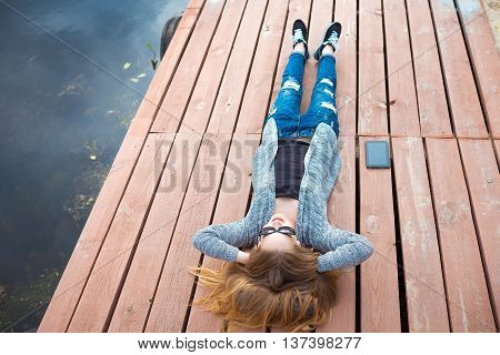 Young woman relaxing on pier. laying on the pier and watching in the sky. listening some music