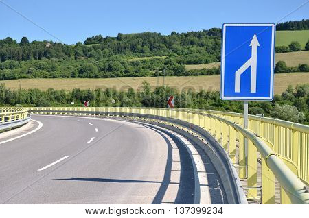 Curved feeder road in countryside white arrow traffic sign in foreground