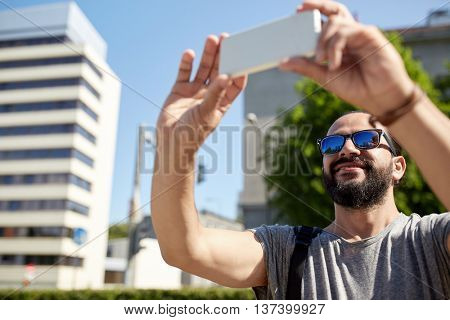 travel, tourism, communication, technology and people concept - smiling man with backpack taking video or selfie by smartphone on summer city street