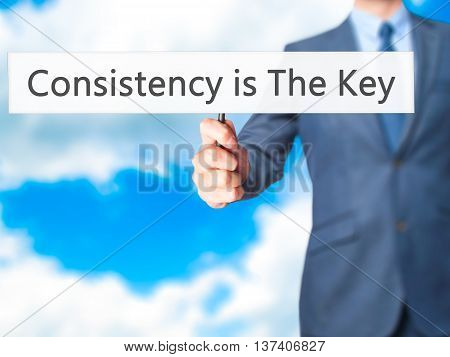 Consistency Is The Key - Business Man Showing Sign