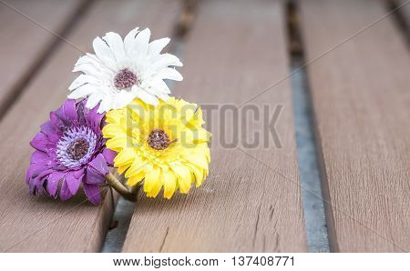 Closeup colorful faked flower for decorate on blurred old wood table textured background