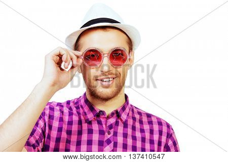 Happy young man in stylish bright clothes and sunglasses smiling at camera. Summer fashion. Isolated over white.