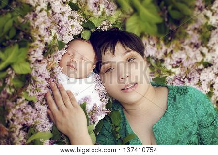 young Asian mother lying with sleeping baby and pats him on floral background of lilac