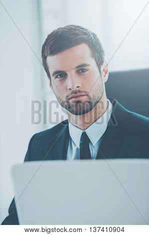 Young and successful. Confident young man in formalwear looking at camera while sitting at his working place