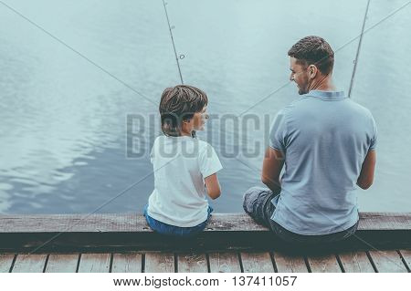 Fishing together is fun. Rear view of father and son fishing while sitting on quayside together