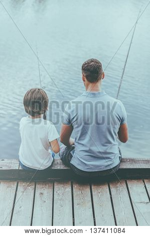 Enjoying day fishing. Rear view of father and son fishing while sitting on quayside together