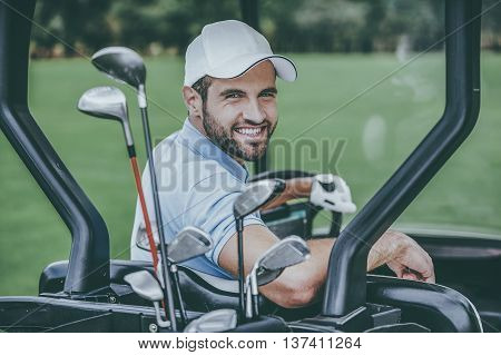 Man in golf cart. Rear view of young happy male golfer driving a golf cart and looking over shoulder