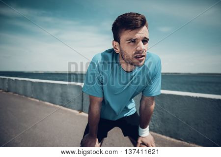Need a break. Tired young man in sports clothes holding hands on knees and looking away while standing outdoors