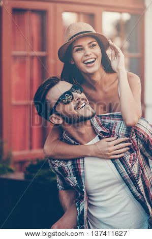 Happy to be together. Happy young man carrying his beautiful girlfriend on shoulders and smiling while walking by the street