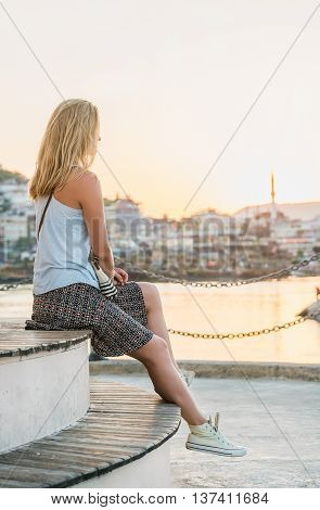 Young blond woman watching sunset near lighthouse in sea port of Alanya, Turkey, Mediterranean region.