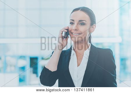 Staying in touch. Beautiful young woman in formalwear talking on the mobile phone and smiling while standing outdoors