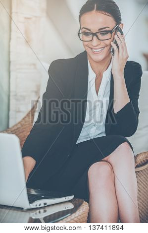 Businesswoman at work. Cheerful young woman in formalwear working on laptop and talking on the mobile phone while sitting at the comfortable chair