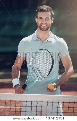Enjoying the game. Happy young man in polo shirt holding tennis racket and ball while standing on tennis court