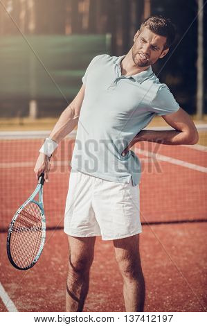 Feeling that pain again. Tennis player touching his back and grimacing while standing on the tennis court