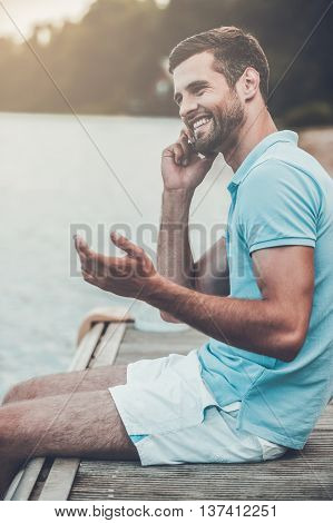 Good talk. Side view of handsome young man talking on the mobile phone and smiling while sitting at the riverbank