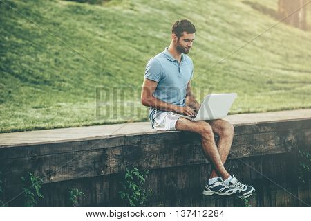Surfing web outdoors. Handsome young man in polo shirt working on laptop while sitting on quayside