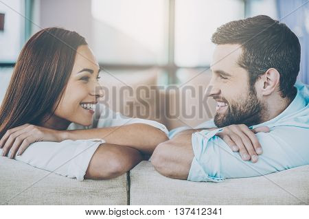 Enjoying every moment together. Beautiful young loving couple sitting together on the couch and looking at each other with smile
