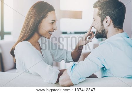 Enjoying every minute together. Playful young loving couple sitting together on the couch and looking at each other with smile while woman touching nose of her boyfriend