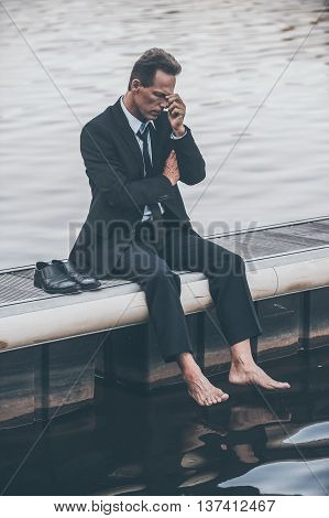 Feeling hopeless. Depressed mature businessman touching his face with hand while sitting barefoot at the quayside