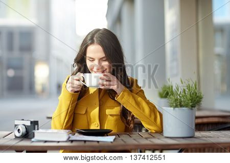 travel, tourism, drinks, leisure and people concept - happy young tourist woman or teenage girl with film camera and guidebook drinking cocoa at city street cafe terrace