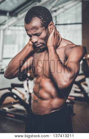 Feeling pain in neck. Frustrated young African man touching his neck and keeping eyes closed while standing in gym