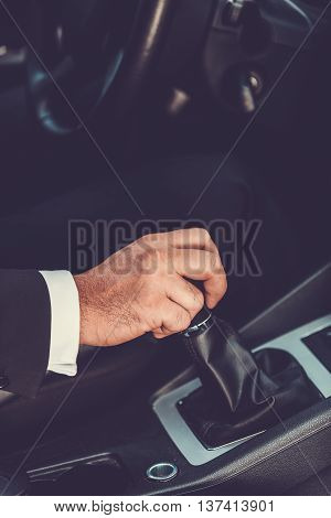 Driving car concept. Close-up of man in formalwear driving car
