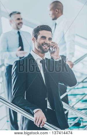 Sharing great news. Low angle view of confident young man in formalwear talking on the mobile phone and smiling while moving down by staircase with people in the background