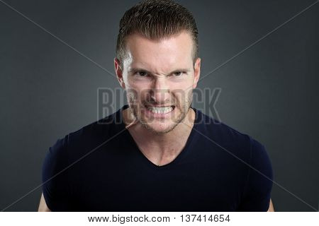 Young man furious over a gray background