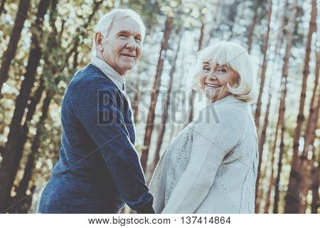 Never get bored together. Rear view of happy senior couple holding hands and looking over shoulder while walking by park together