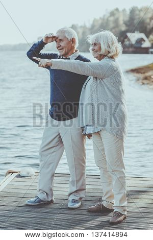 What is that? Full Length of happy senior couple standing on the quayside together while woman pointing away and smiling