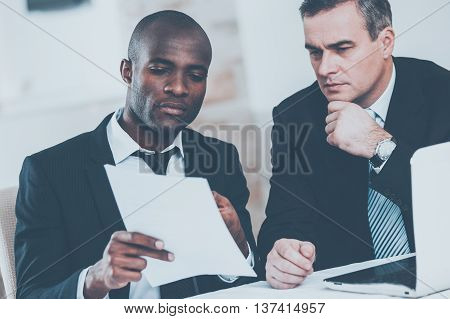 Discussing business together. Two confident business people in formalwear discussing something while one of them pointing a paper
