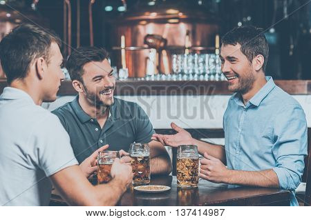 Sharing the latest news. Three cheerful friends drinking beer and chatting in bar
