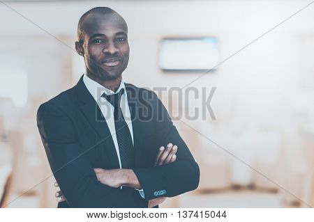 Confident and successful. Cheerful young African man in full suit keeping arms crossed and looking at camera
