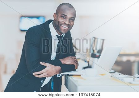 Young and successful. Cheerful young African man in formalwear using his laptop while leaning at bar