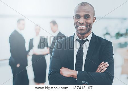 Confident and successful businessman. Cheerful young African man in formalwear keeping arms crossed and smiling while his colleagues standing on background